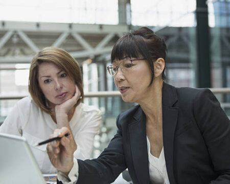 A photo of a financial advisor pointing something out to a client on a computer monitor.